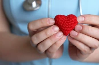 A nurse holds a heart