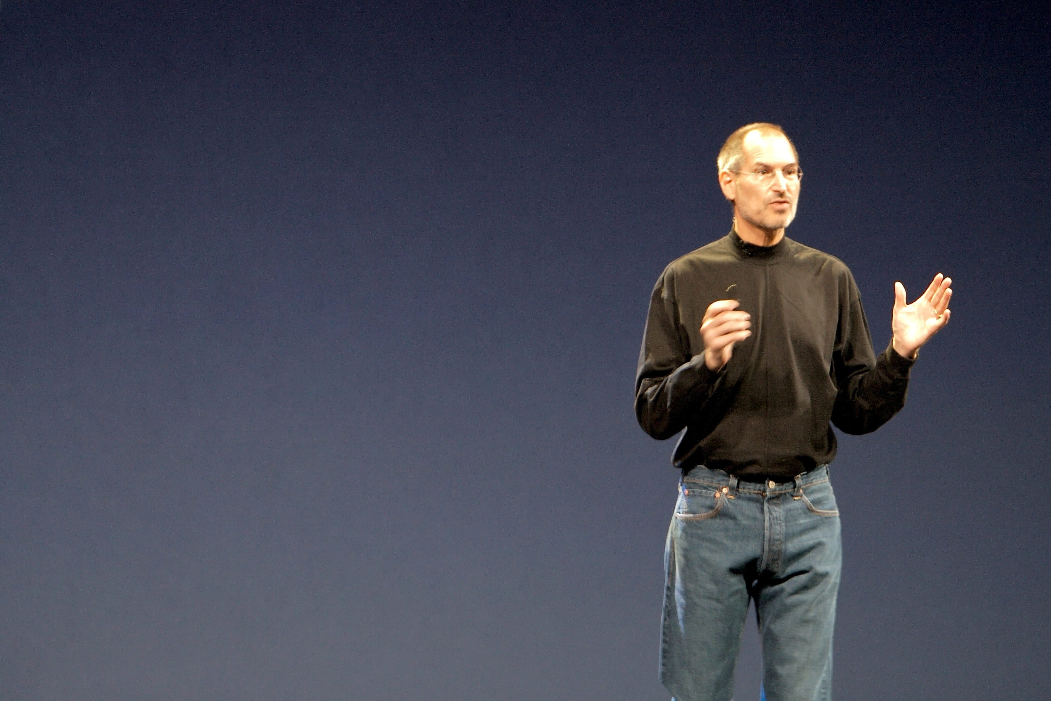 Steve Jobs gives a presentation while wearing a black turtleneck on stage.