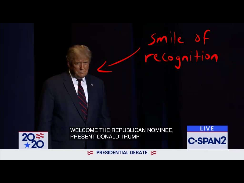 Trump walks on stage while flashing a smile