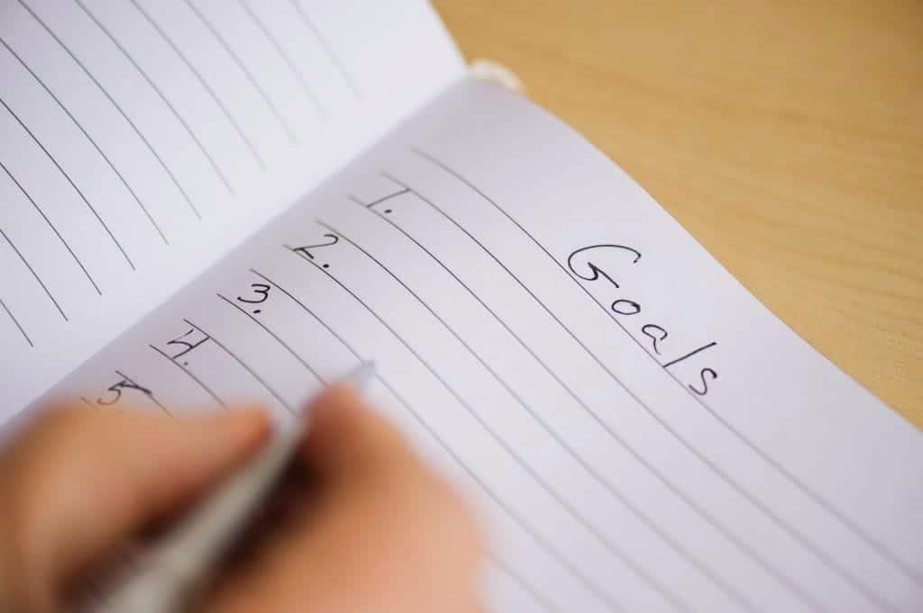 C-level executive's hand, writing a goal list