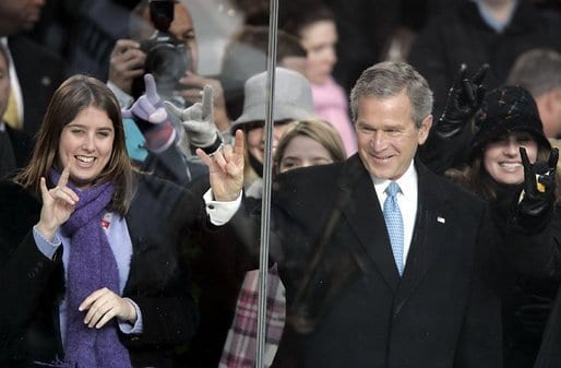 """President George W. Bush hand gestures the 'Hook 'em, horns,"""" the salute of the University of Texas Longhorns,"""