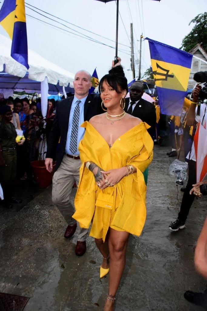 Rihanna walking through a crowd as she holds her micro purse in front of her. with her arms corssed