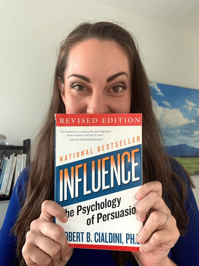 Vanessa van Edwards holding the book  Influence: The Psychology of Persuasion