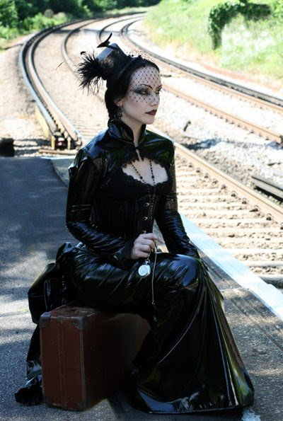 Goth woman sitting on a suitcase by the railway