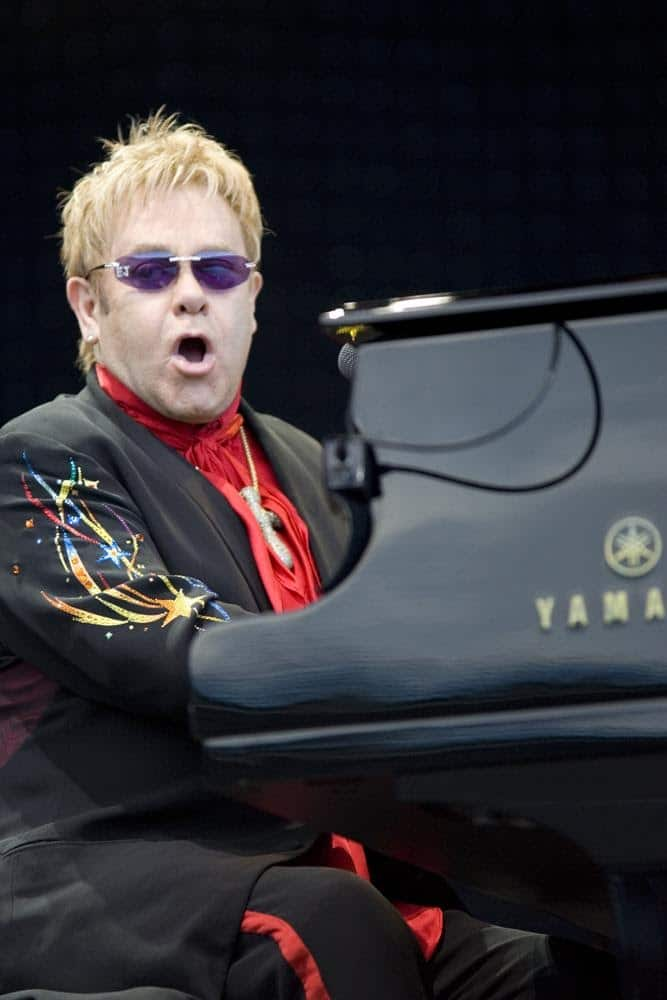 Elton John playing the piano and singing