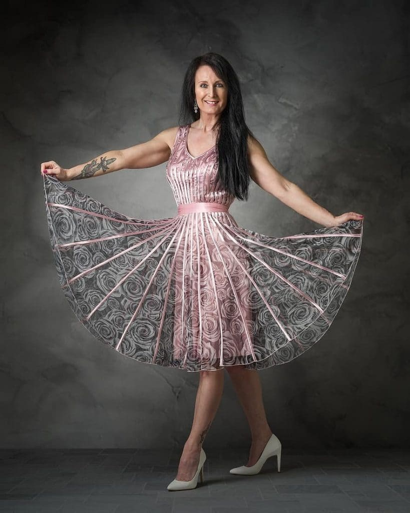 happy standing woman showing her dress