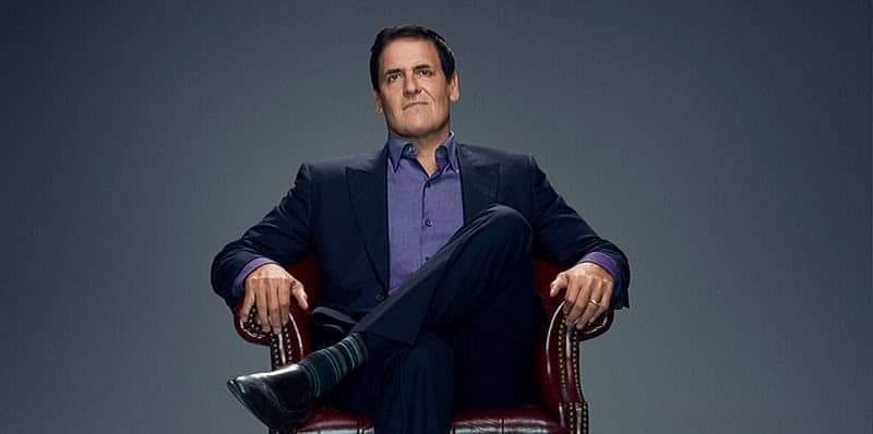 Mark Cuban with his legs in the figure 4 position