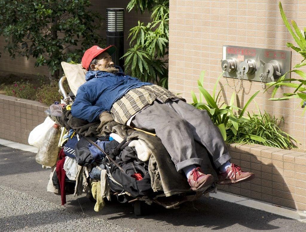 homeless man sleeping on a trolly