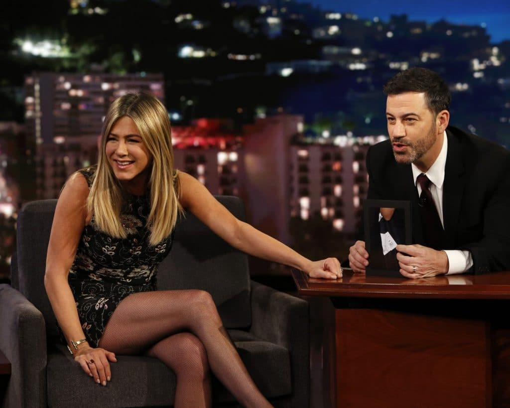 Jennifer Aniston Plays at Jimmy Kimmel show crossing her legs