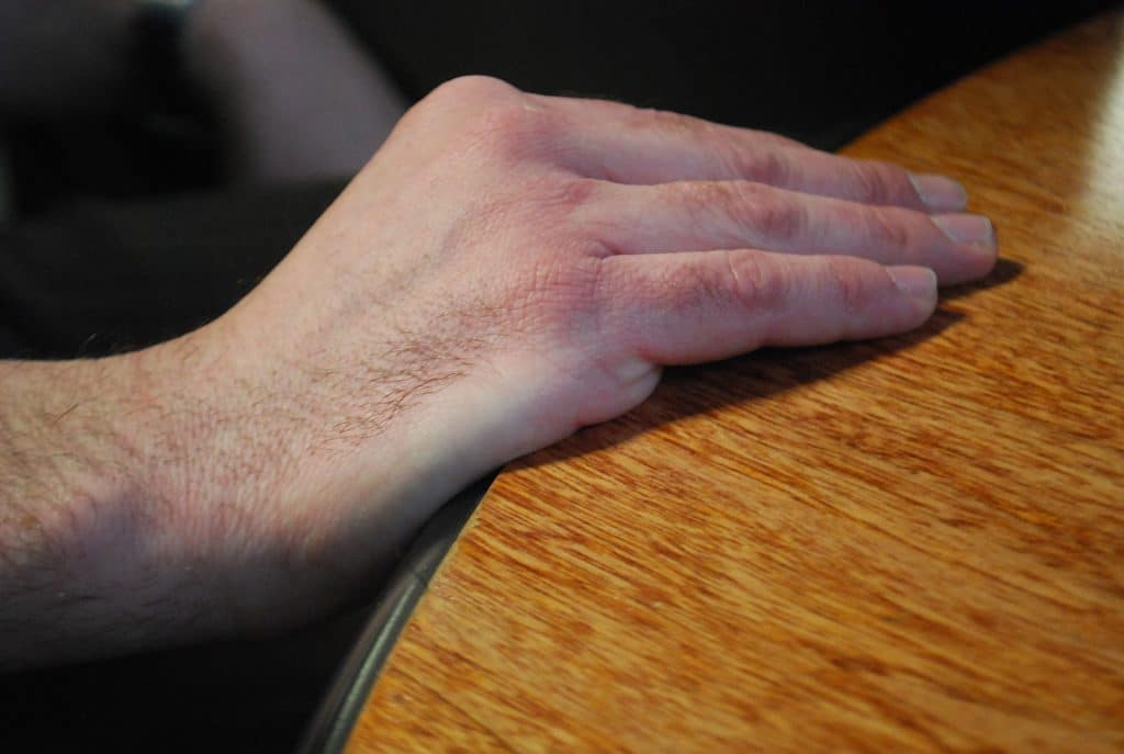 Hand resting on table body language cue