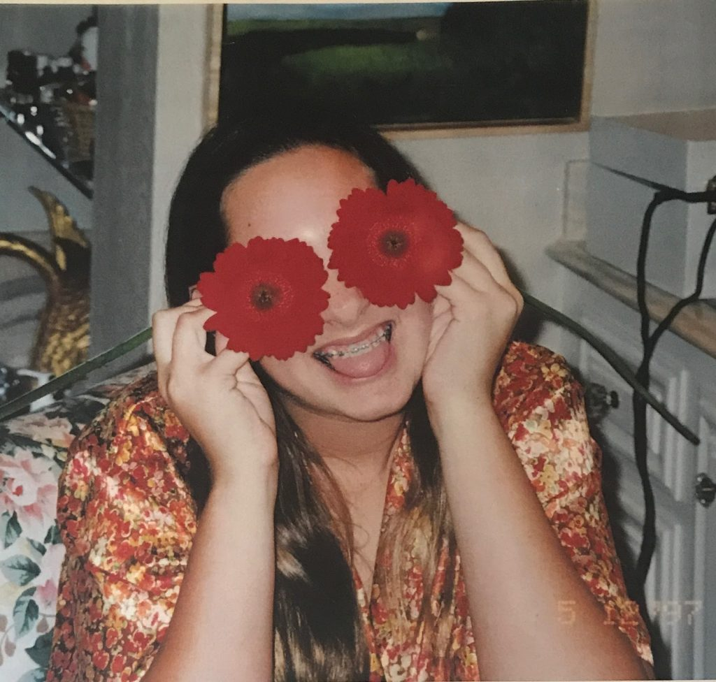 Young Vanessa trying to hide from her awkwardness holding flowers in front of her eyes