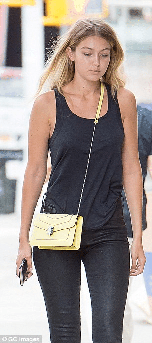 confident body language Gigi Hadid using her purse as a defense.