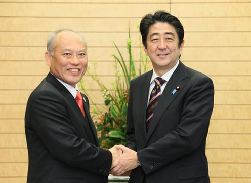 Japanese leader Shinzo Abe gets a hand up on Yoichi Masuzoe