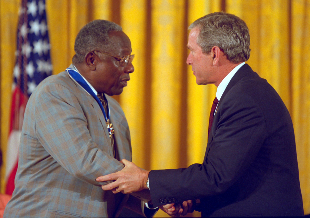 Image of President Bush shaking hands with baseball legend Hank Aaron, in a dominant way