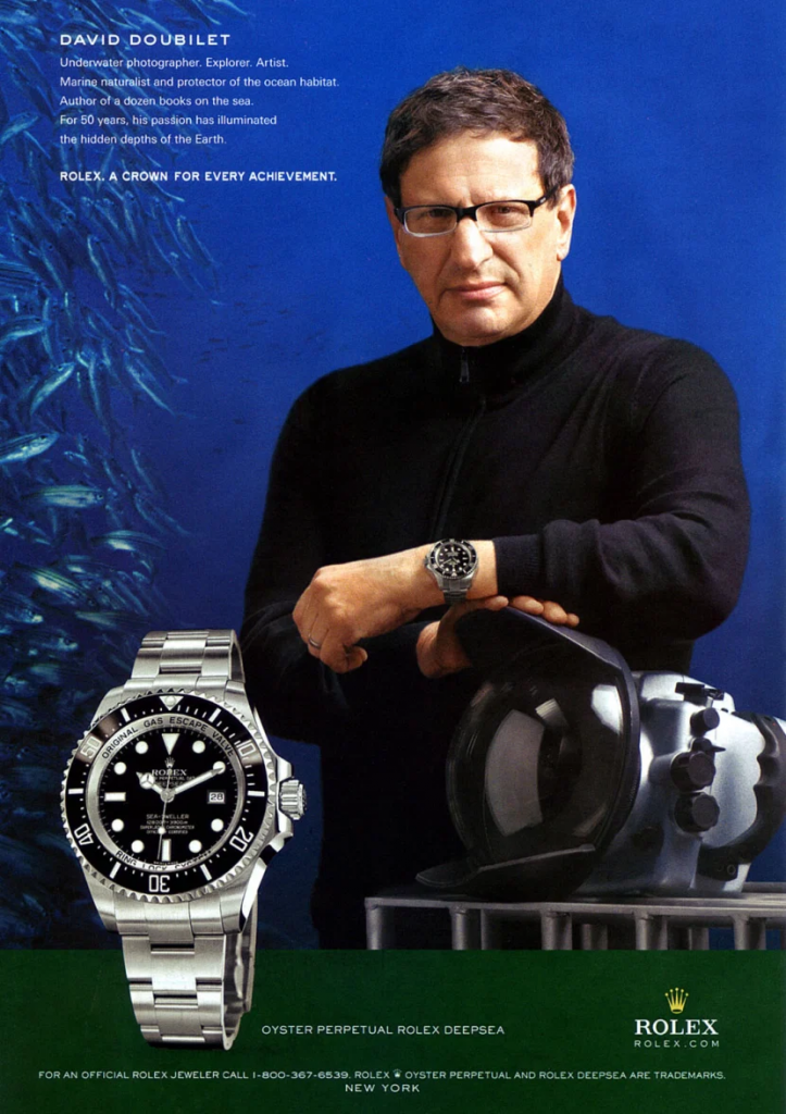 Image of a Rolex ad, the man in it is wearing a black turtleneck sweater and a rolex